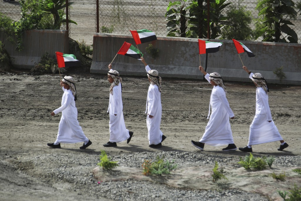 Young boys wave Emirati flags at the opening ceremony of the International Defense Exhibition and Conference in Abu Dhabi, United Arab Emirates, Sunda...