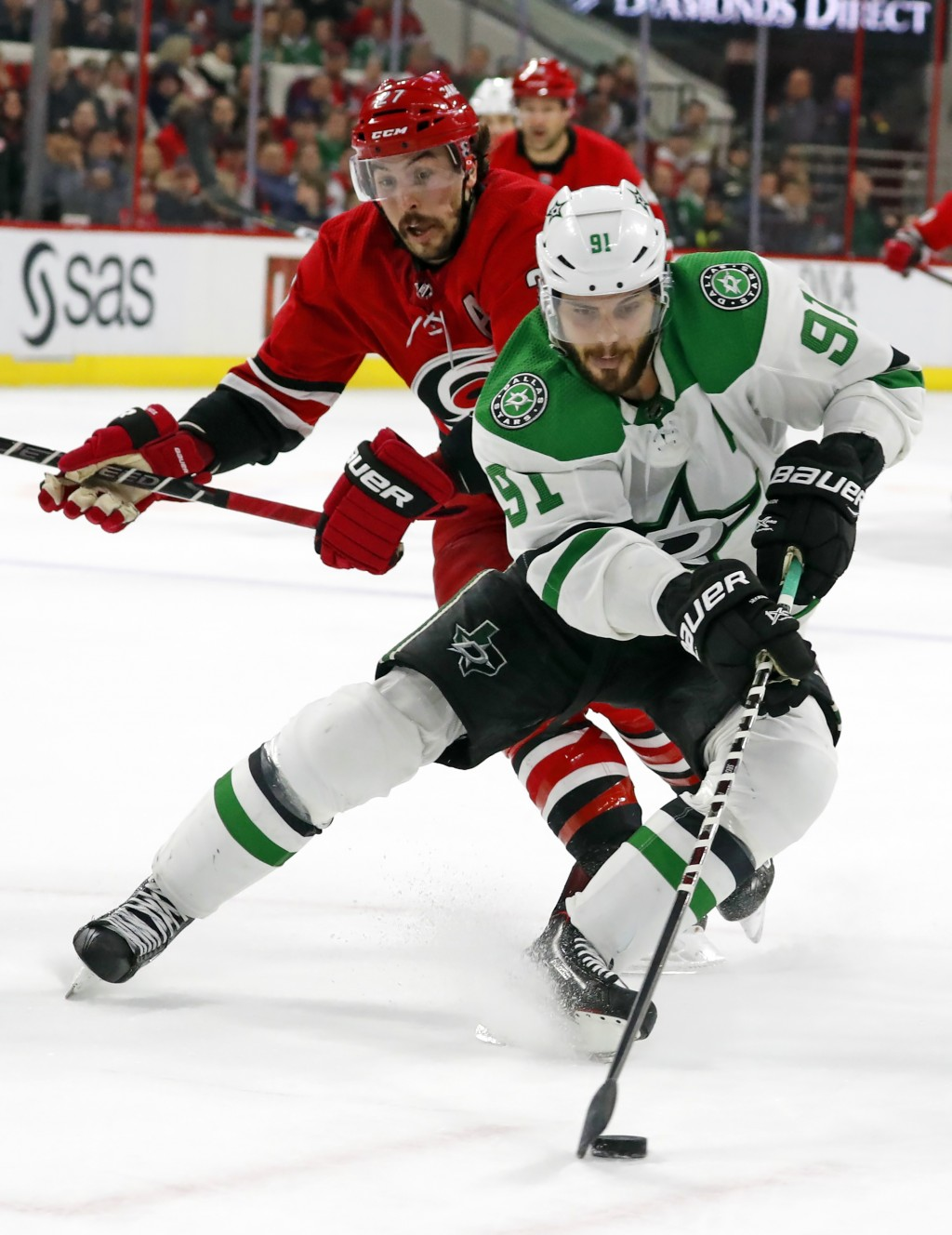 Dallas Stars' Tyler Seguin (91 controls the puck in front of Carolina Hurricanes' Justin Faulk (27) during the second period of an NHL hockey game, Sa...