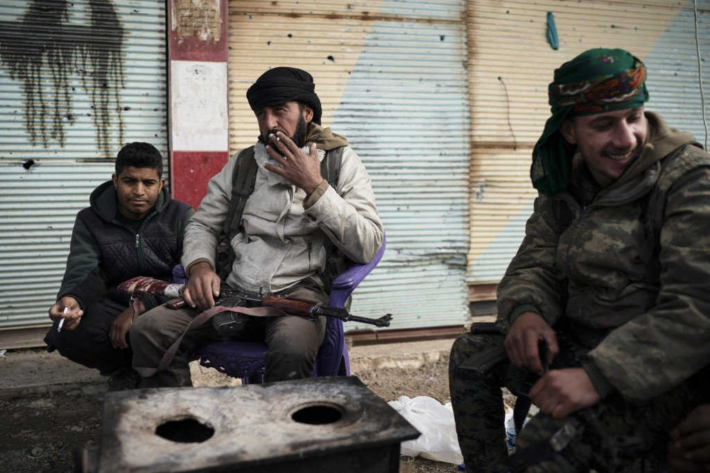 U.S.-backed Syrian Democratic Forces (SDF) fighters sit outside a building as fight against Islamic State militants continue in the village of Baghouz...