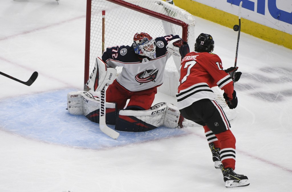 Columbus Blue Jackets goaltender Sergei Bobrovsky (72) defends against Chicago Blackhawks center Dylan Strome (17), who tries to knock down the puck d...