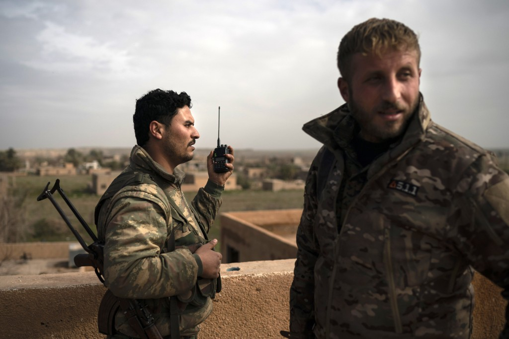 U.S.-backed Syrian Democratic Forces (SDF) fighters talk on a radio in a rooftop position as fight against Islamic State militants continues in the vi...