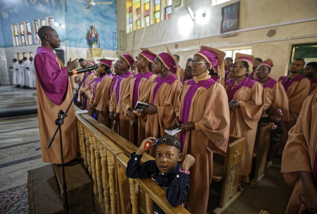 The son of one of the choristers stands with the choir during a morning service at the Saint Charles Catholic Church, the site of a 2014 bomb attack b...