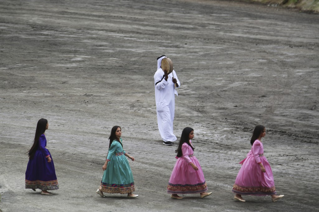 Young girls walk past an Emirati man playing a traditional drum at the opening ceremony of the International Defense Exhibition and Conference in Abu ...