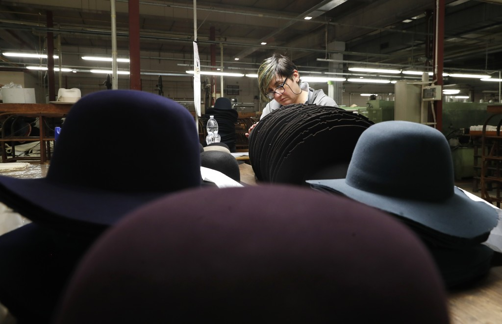 A woman works on hats inside the Borsalino hat factory, in Spinetta Marengo, near Alessandria, Italy, Thursday, Jan. 17, 2019. Borsalino's prized felt...