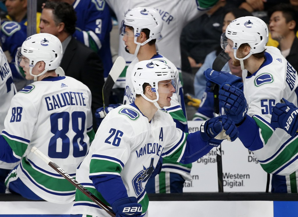 Vancouver Canucks' Antoine Roussel (26) celebrates with Guillaume Brisebois (56) after scoring against the San Jose Sharks during the first period of ...