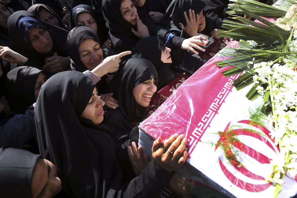 Mourners reach out to touch the caskets of those killed in a suicide car bombing that targeted members of Iran's powerful Revolutionary Guard in earli...