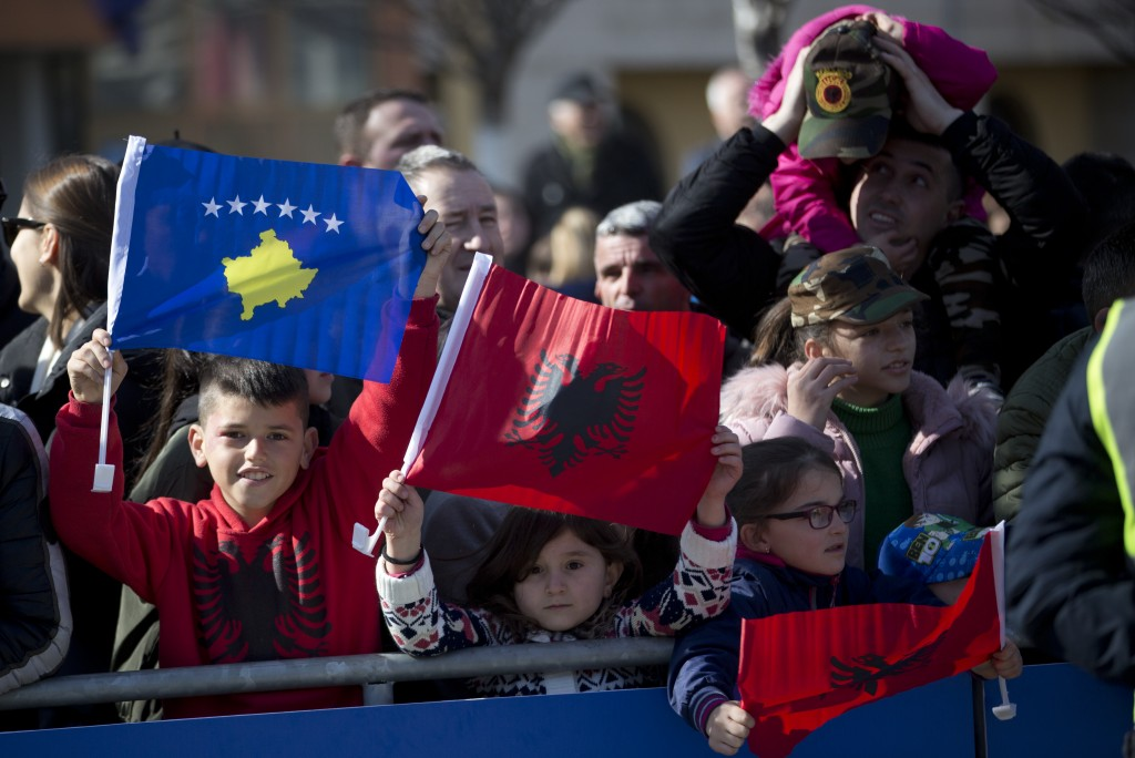 Kosovars waving national flags pose for a photo, during celebrations to mark the 11th anniversary of independence, in Pristina, Sunday, Feb. 17, 2019....