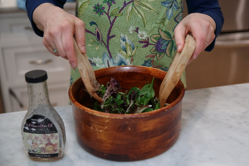 Sen. Kirsten Gillibrand, D-N.Y., tosses a salad as she prepares dinner at her home in Washington, Tuesday, Feb. 12, 2019. Gillibrand isn't just embrac...