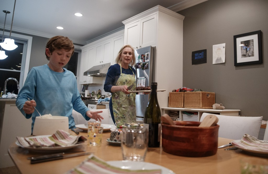 Sen. Kirsten Gillibrand, D-N.Y., and her son Henry Gillibrand set the table for dinner in their home in Washington, Tuesday, Feb. 12, 2019. Gillibrand...