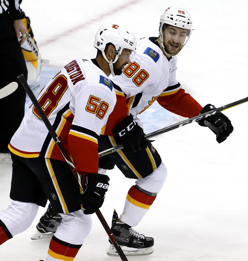 Calgary Flames' Andrew Mangiapane (88) celebrates his goal with Oliver Kylington (58) during the first period of an NHL hockey game against the Pittsb...