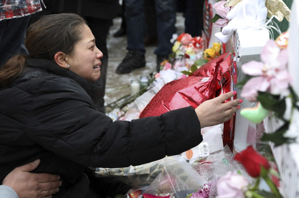 One of victim Vicente Juarez's daughter Diana Juarez cries as she touch a cross at a makeshift memorial Sunday, Feb. 17, 2019, in Aurora, Ill., near H...