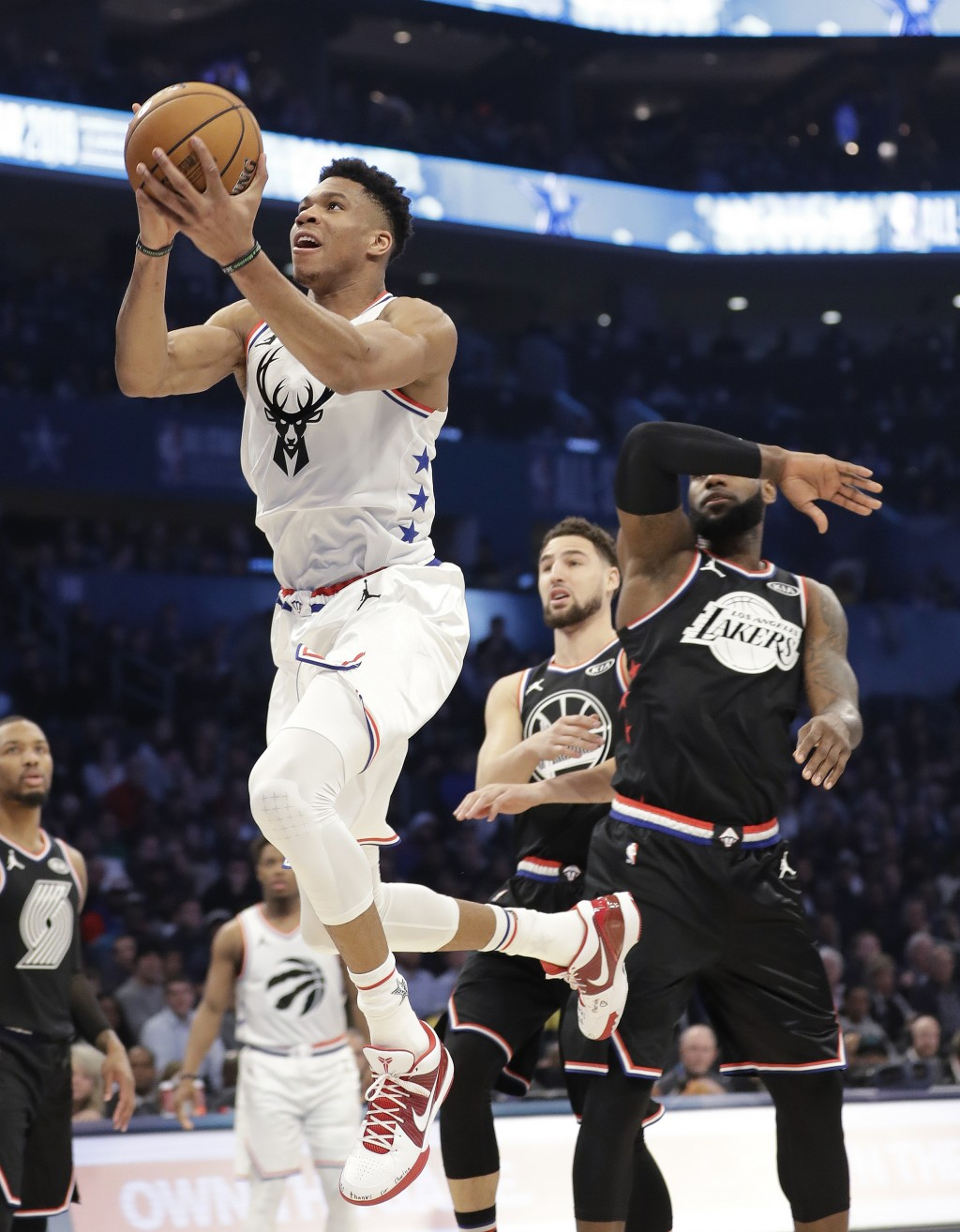 CORRECTS TO THE LAKERS, NOT THE CAVALIERS - Team Giannis' Giannis Antetokounmpo, of the Milwaukee Bucks, moves past Team LeBron's LeBron James, of the