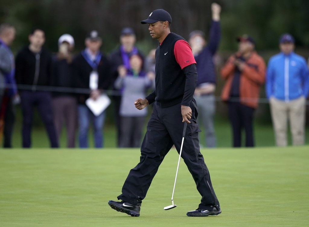 Tiger Woods fist-pumps after making a putt for eagle on the first hole as third-round play continues during the Genesis Open golf tournament at Rivier...