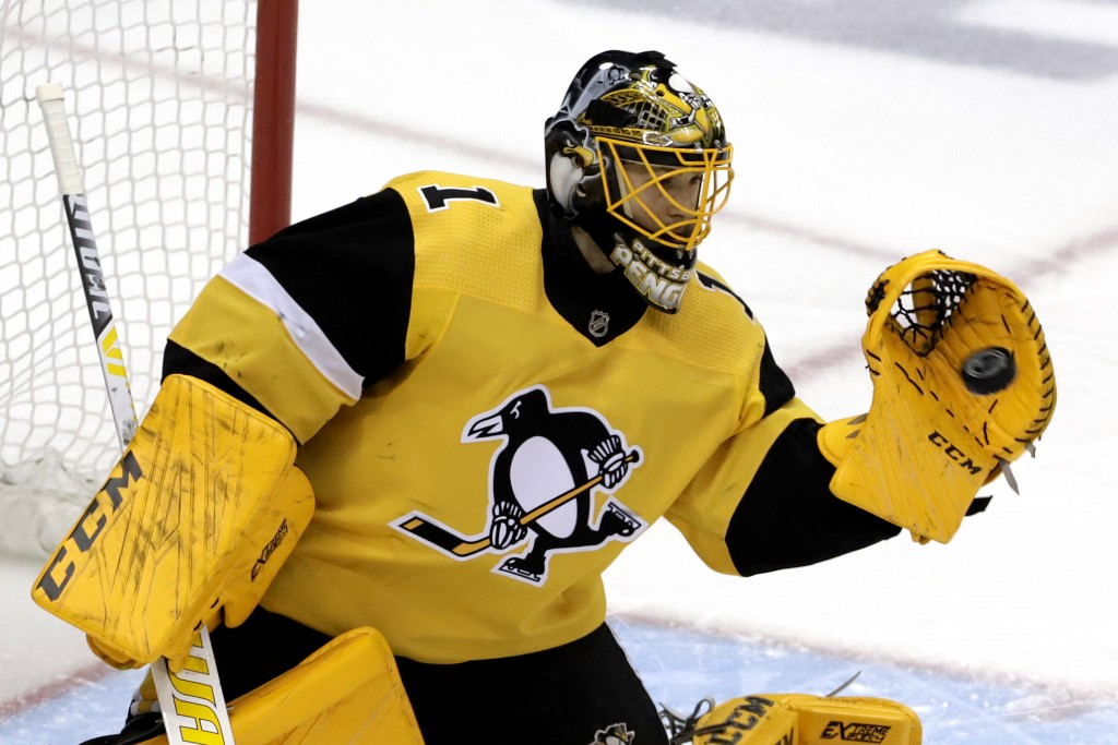 Pittsburgh Penguins goaltender Casey DeSmith gloves a shot during the first period of an NHL hockey game against the New York Rangers in Pittsburgh, S...