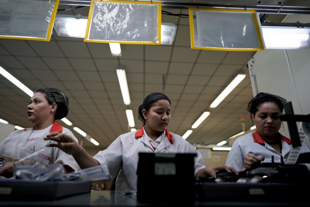 Landineia Silva, center, works assembling cell phone batteries at the Salcomp factory in Manaus, Brazil, Thursday, Feb. 14, 2019. Silva and many of he...