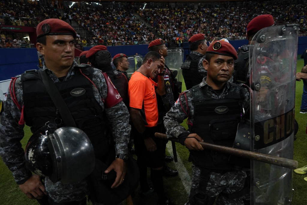 In this Saturday, Feb. 16, 2019 photo, police protect referee Moacir Eriberto Guedes during the Peladao final amateur soccer tournament at Arena da Am...