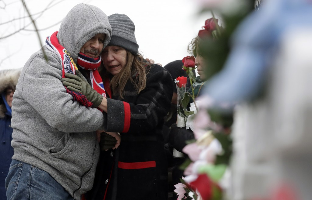 People attend at a makeshift memorial Sunday, Feb. 17, 2019, in Aurora, Ill., near Henry Pratt Co. manufacturing company where several were killed on