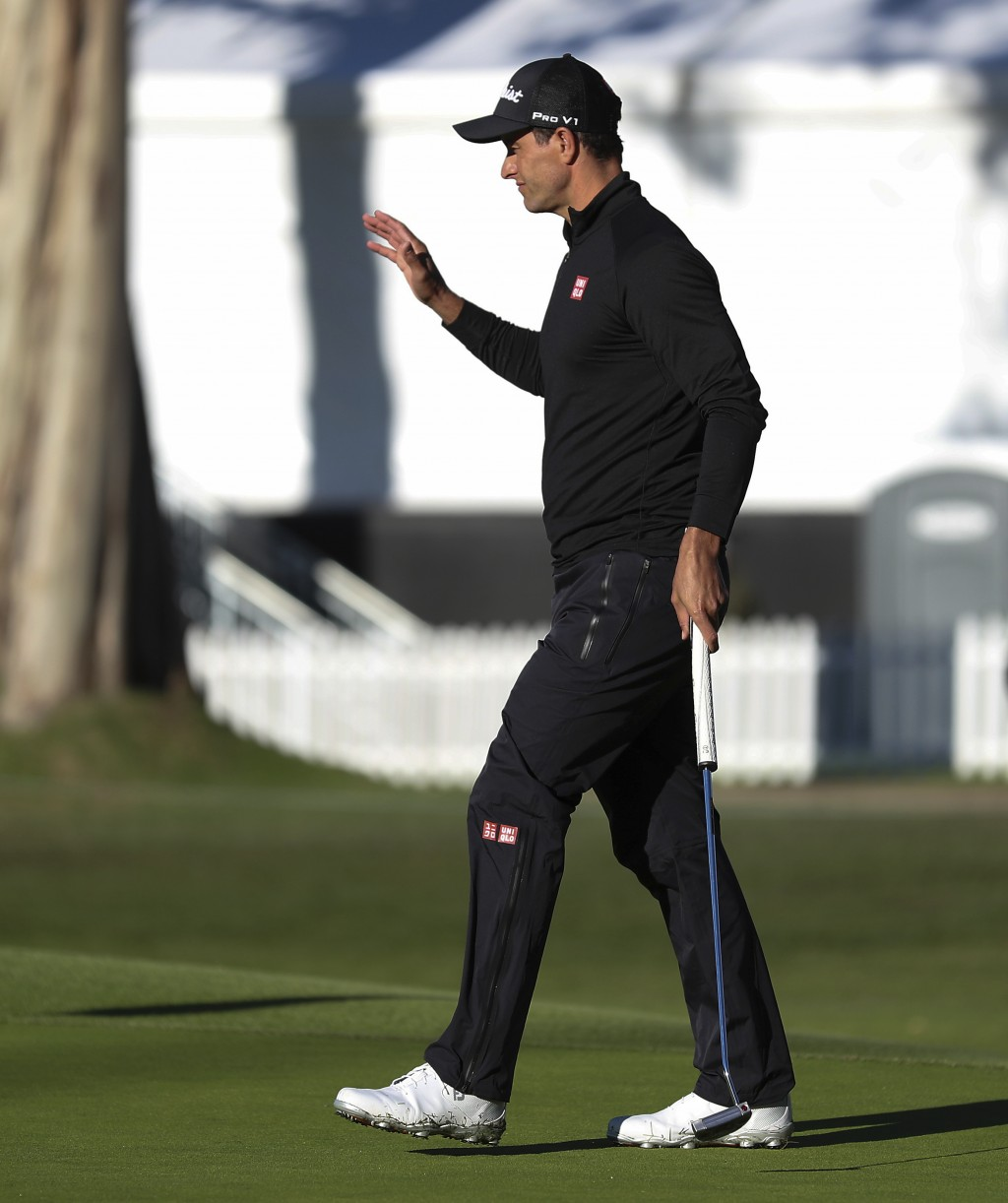 Adam Scott, of Australia, waves to the crowd after making a birdie putt on the eighth hole as third-round play continues during the Genesis Open golf ...