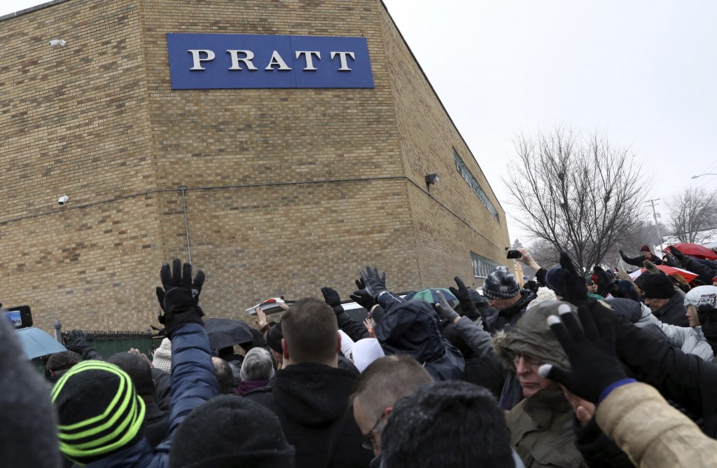 Family, friends and community members attend a vigil Sunday, Feb. 17, 2019, in Aurora, Ill. Six people, including a gunman, died in a shooting at a ma