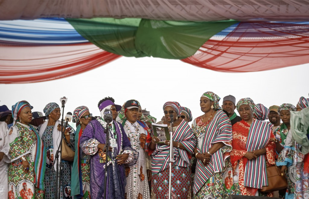 In this photo taken Wednesday, Feb. 13, 2019, women party members and officials take the stage to speak at a rally for incumbent President Muhammadu B