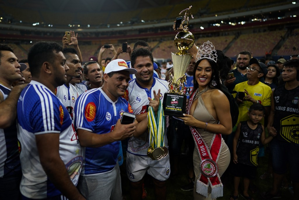 Alvorada soccer team players and staff pose with beauty Queen Isabelle Nogueira who holds their trophy after winning the Peladao amateur soccer tourna...