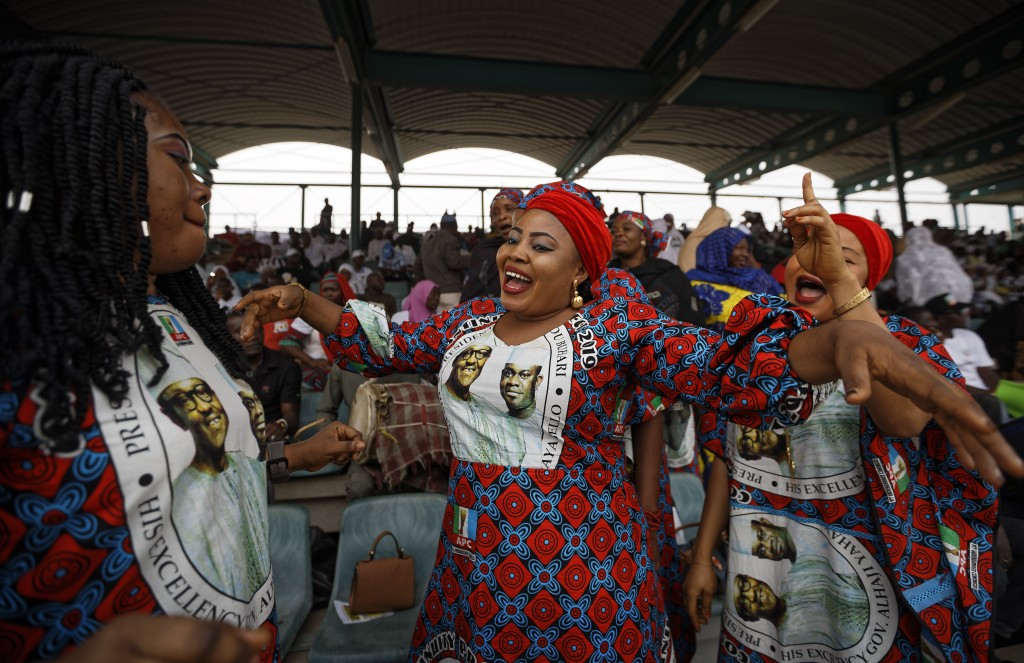 FILE - In this Wednesday, Feb. 13, 2019 file photo, supporters of incumbent President Muhammadu Buhari sing and dance in advance of his arrival at a c