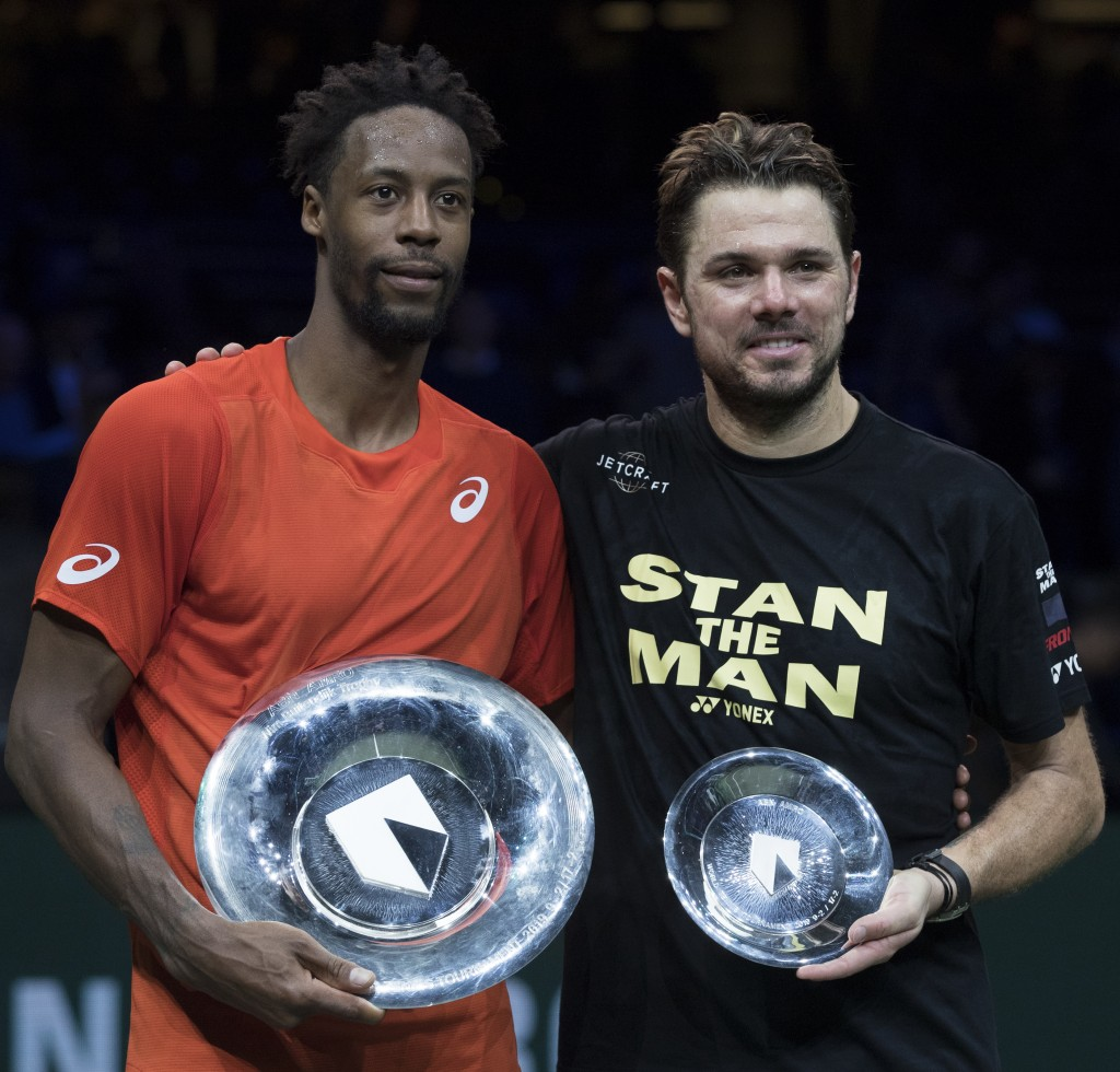 Gael Monfils of France holds the trophy as he celebrates winning against Stan Wawrinka of Switzerland, right, in three sets, 6-3, 1-6, 6-2, in the men...