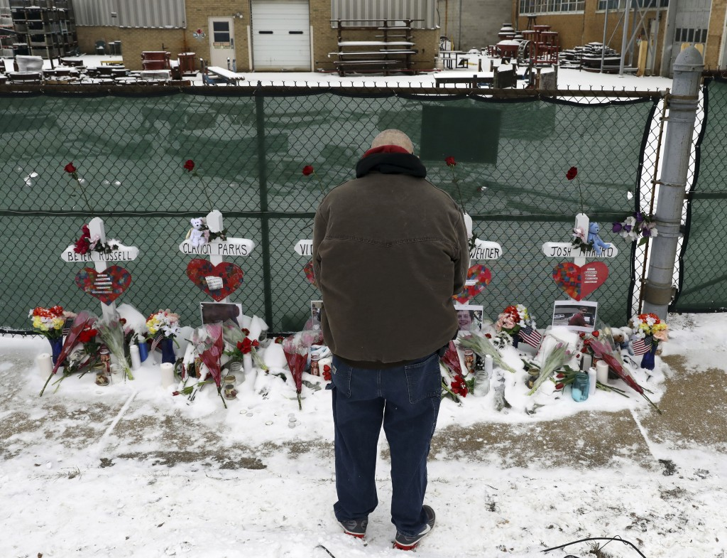 A man prays at a makeshift memorial Sunday, Feb. 17, 2019, in Aurora, Ill., near Henry Pratt Co. manufacturing company where several were killed on Fr...