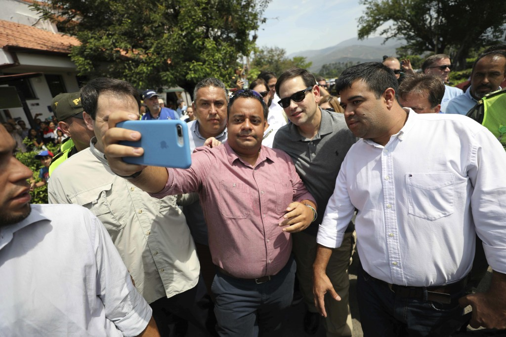 U.S. Senator Marco Rubio, R-Fla., in sunglasses, poses for photos with people near the Simon Bolivar International Bridge, which connects Colombia wit...