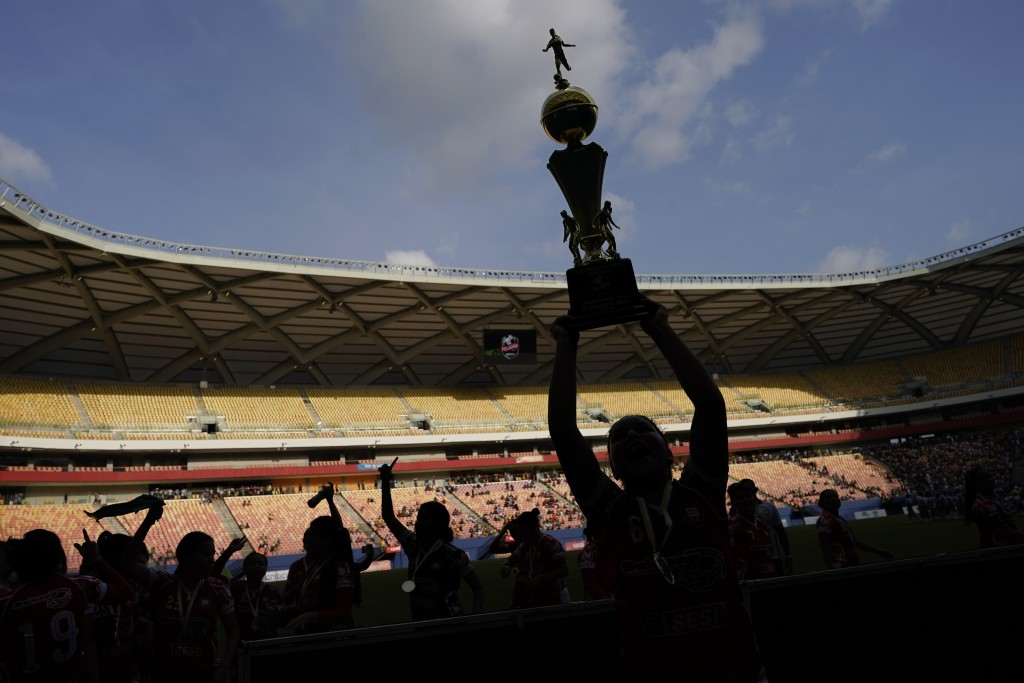 Salcomp players celebrate with their trophy after winning the Peladao amateur soccer tournament at Arena da Amazonia in Manaus, Brazil, Saturday, Feb....