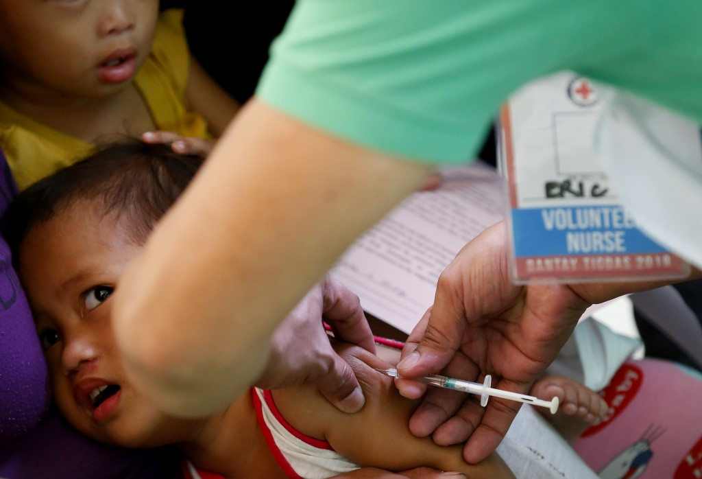 FILE - In this Feb. 16, 2019, file photo, Philippine National Red Cross and Health Department volunteers conduct house-to-house measles vaccination to