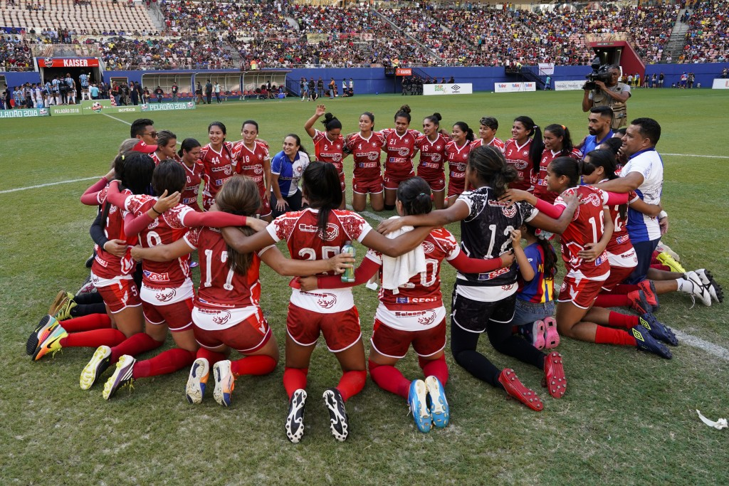 Salcomp players huddle at the center of the pitch of Arena da Amazonia after winning the Peladao amateur soccer tournament in Manaus, Brazil, Saturday...