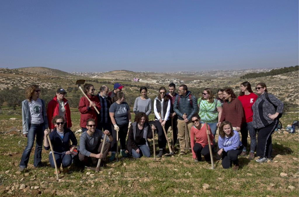 In this Friday, Jan. 25, 2019 photo, American rabbinical students take a group photo,  with the village of Attuwani in the background, during a day pl