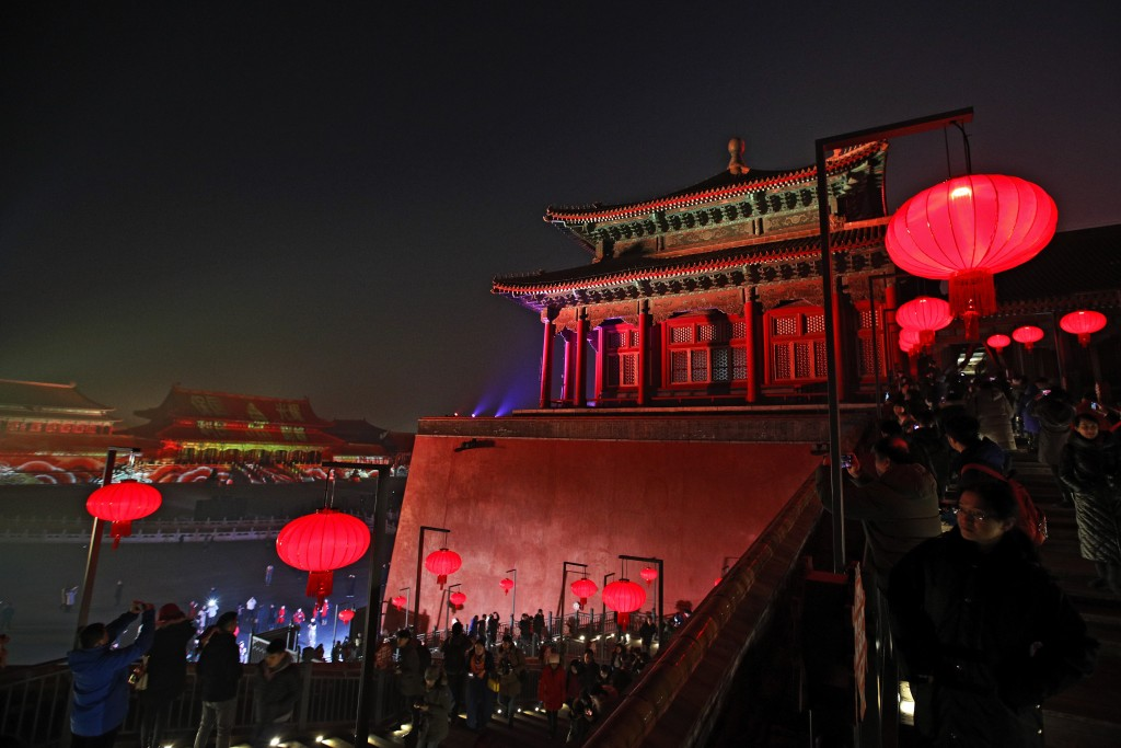 Visitors tour the Forbidden City decorated with red lanterns and illuminated with lights during the Lantern Festival in Beijing, Tuesday, Feb. 19, 201...
