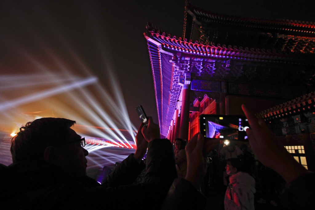 Visitors take souvenir photos of the Forbidden City illuminated with lights during the Lantern Festival in Beijing, Tuesday, Feb. 19, 2019. Beijing's ...