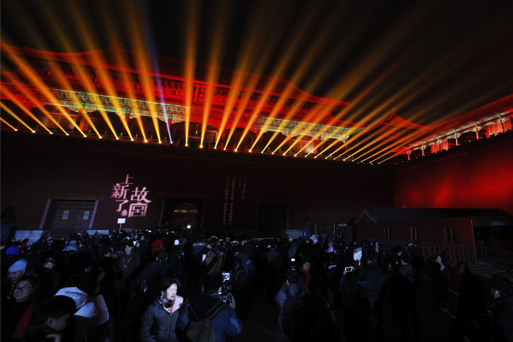 Visitors watch the Wumen Gate wall of the Forbidden City is illuminated during the Lantern Festival in Beijing, Tuesday, Feb. 19, 2019. Beijing's Pala...