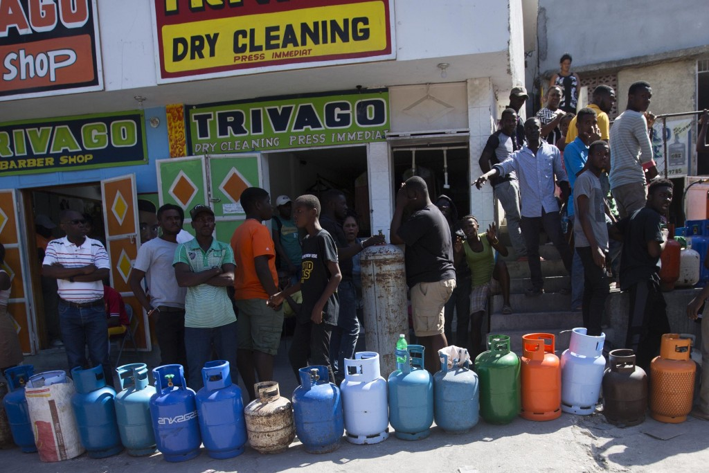Residents line up to buy propane gas in Port-au-Prince, Haiti, Monday, Feb. 18, 2019. Businesses and government offices slowly reopened across Haiti o