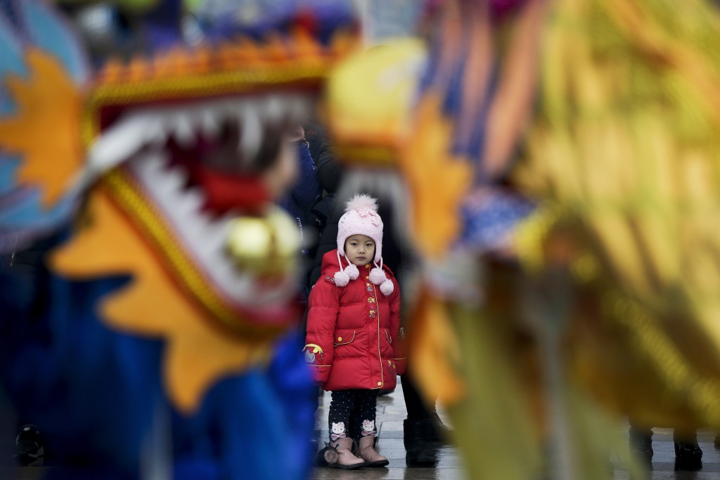 In this Tuesday, Feb. 19, 2019, file photo, a child watches dragon dance performance during the Lantern Festival organized by city government at a squ...