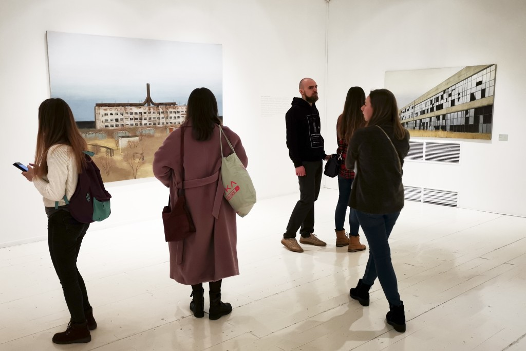 In this photo taken on Sunday, Feb. 17, 2019, visitors attend an exhibition by Russian artist Pavel Otdelnov in Moscow, Russia . Pavel Otdelnov, a Rus