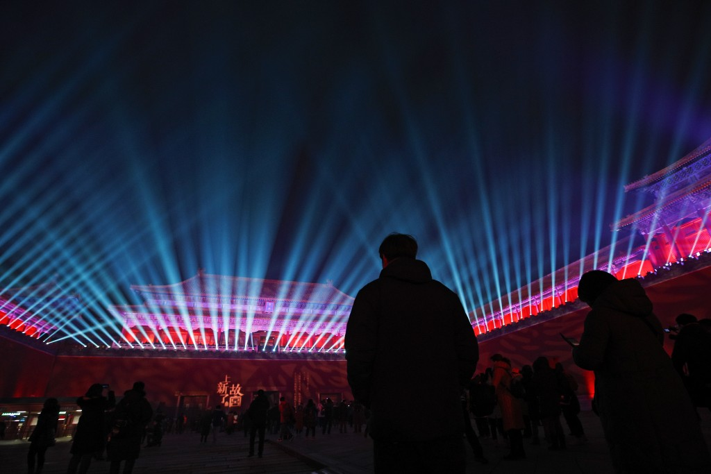 In this Tuesday, Feb. 19, 2019, file photo, visitors watch the Wumen Gate wall of the Forbidden City illuminated with lights for the Lantern Festival ...