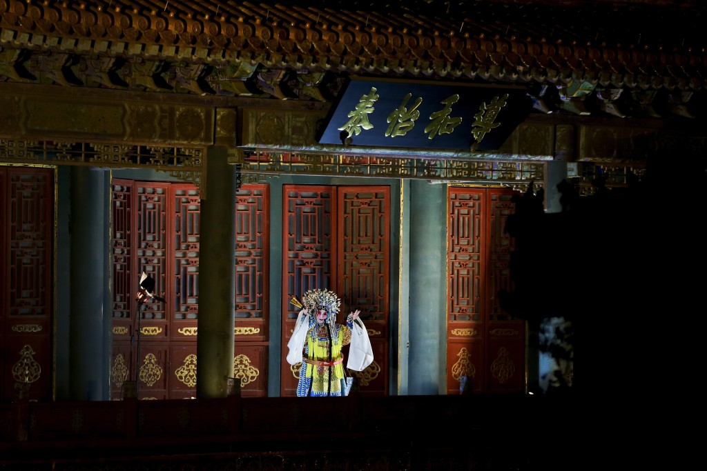 In this Tuesday, Feb. 19, 2019, photo, a Peking Opera artist performs in the Forbidden City which lit up by lights for the Lantern Festival in Beijing