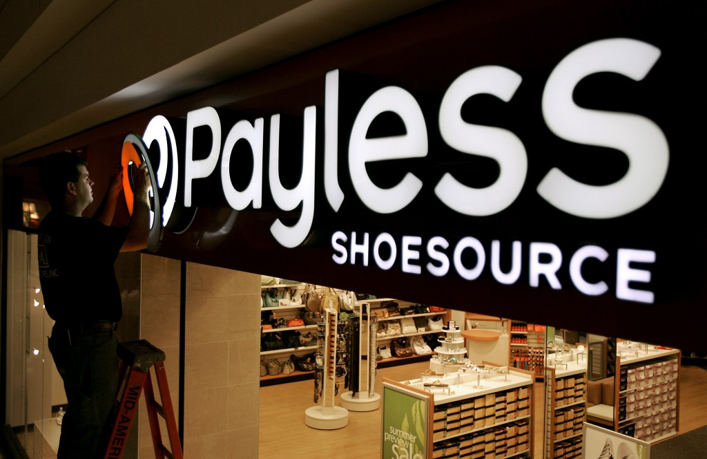 FILE- In this May 18, 2006, file photo a worker puts the finishing touches on a sign unveiling the company's new look at a Payless Shoesource store at