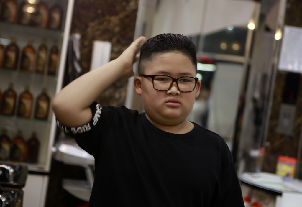 To Gia Huy, 9 checks his hair after having a Kim haircut in Hanoi, Vietnam, on Tuesday, Feb. 19, 2019. U.S. President Donald Trump and North Korean le...