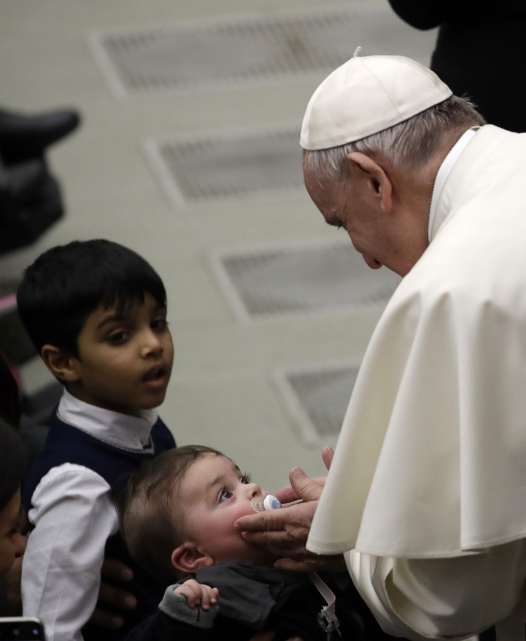 Pope Francis caresses a child during his weekly general audience in the Paul VI Hall at the Vatican Wednesday, Feb. 20, 2019. (AP Photo/Alessandra Tar