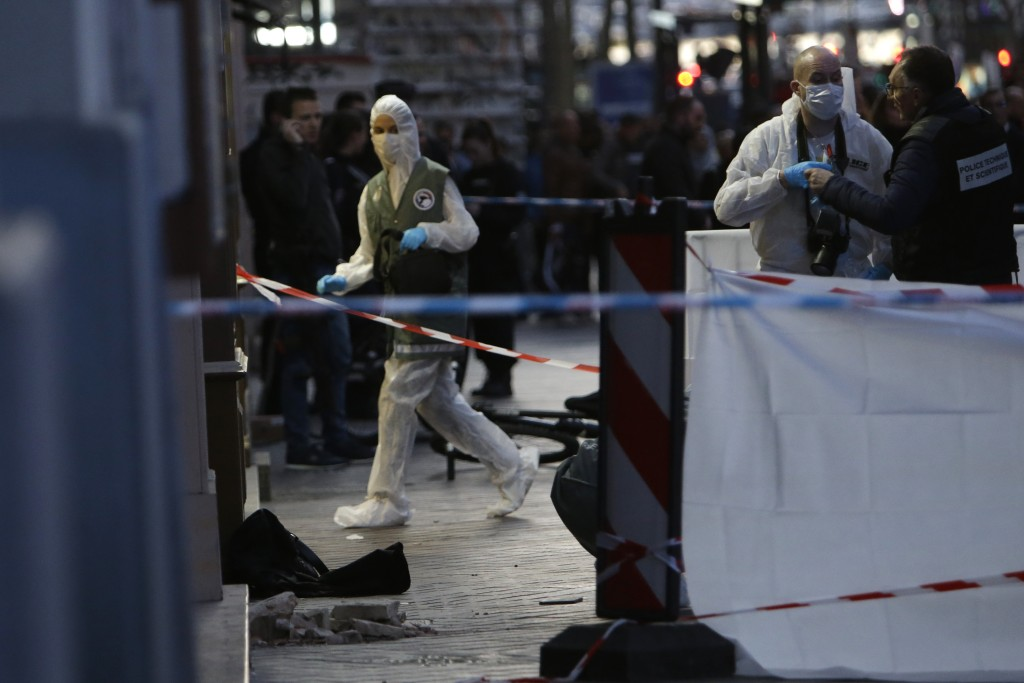 Investigating police officers work at the scene, after an incident, in Marseille, southern France, Tuesday, Feb. 19, 2019. (AP Photo/Claude Paris)