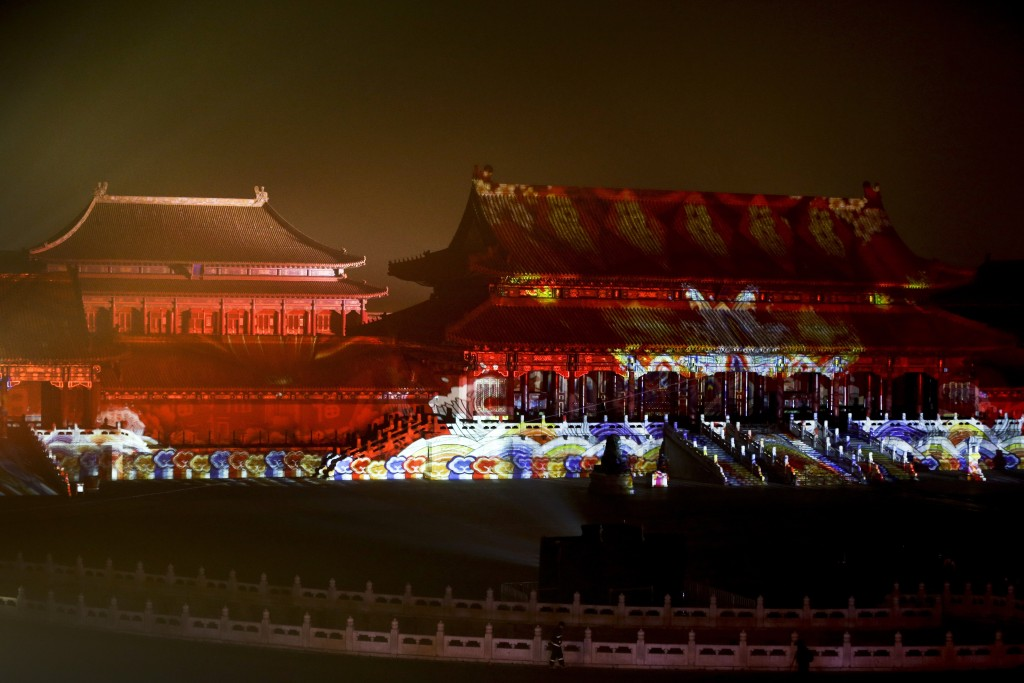 In this Tuesday, Feb. 19, 2019, photo, a firefighter walks by the Forbidden City projected with colourful lights for the Lantern Festival in Beijing.
