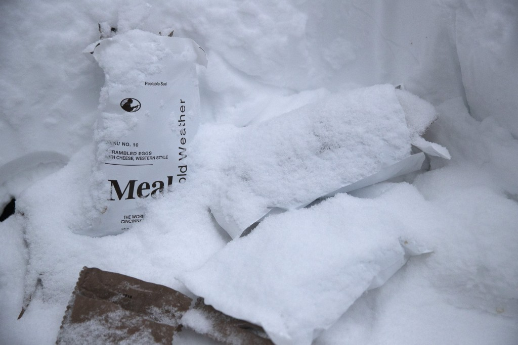 Empty MRE packages are covered in snow as U.S. Marines prepare for advanced cold-weather training at the Marine Corps Mountain Warfare Training Center...