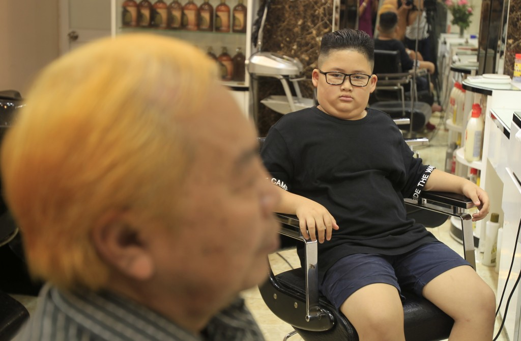 In this Tuesday, Feb. 19, 2019, file photo, Le Phuc Hai, 66, left, and To Gia Huy, 9, sit after having Trump and Kim haircuts in Hanoi, Vietnam.  U.S.