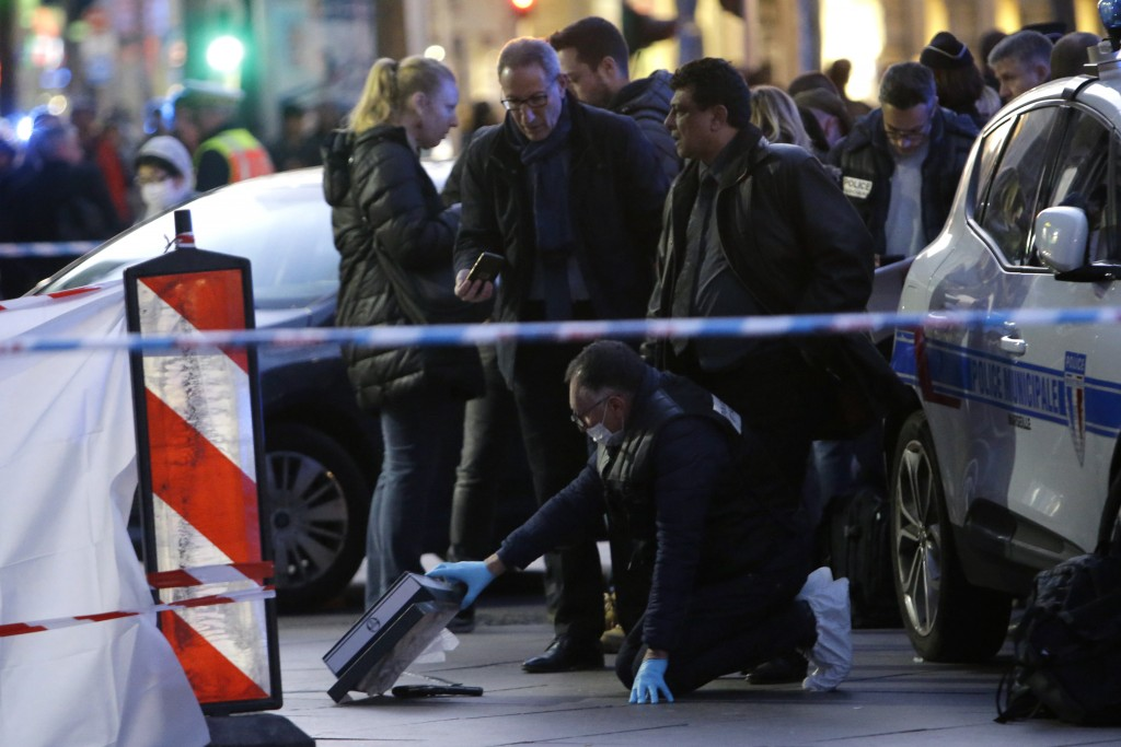 A police officer picks up a gun on the pavement, after an incident, in Marseille, southern France, Tuesday, Feb. 19, 2019. (AP Photo/Claude Paris)