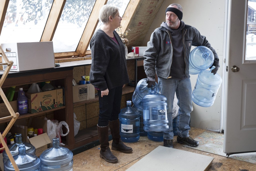 Catherine Maynard, a natural resource analyst for the U.S. Department of Agriculture, receives a bottled water delivery at her home in Rimini, Mont.,